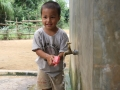 A boy in Quang Tri washing his hands with soap in a community cement tank